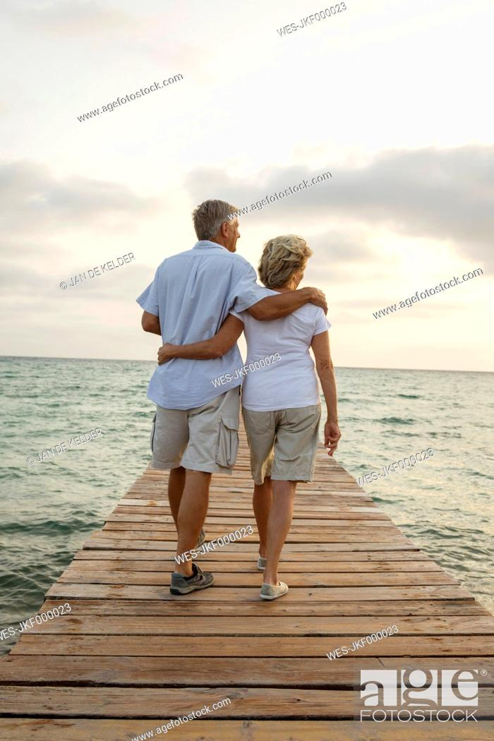 Stock Photo: Spain, Senior couple standing on jetty at the sea.