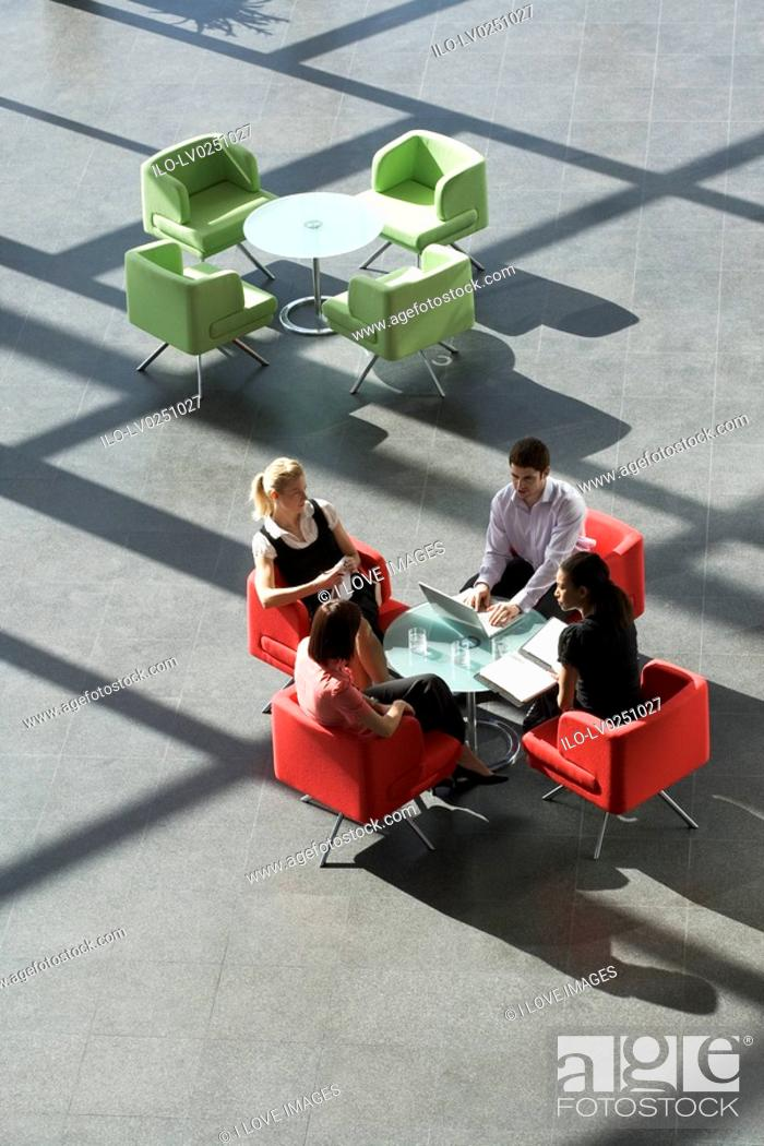 Stock Photo: Four business colleagues holding a business meeting.