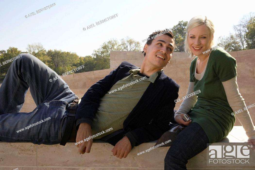 Stock Photo: Couple sitting outdoors smiling with the woman holding a camera.