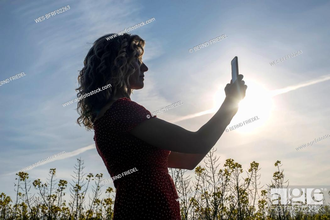 Stock Photo: Silhouette mature woman using smart phone while standing against sky at sunset.
