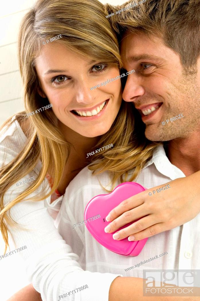 Stock Photo: Portrait of a young woman embracing a mid adult man from behind.