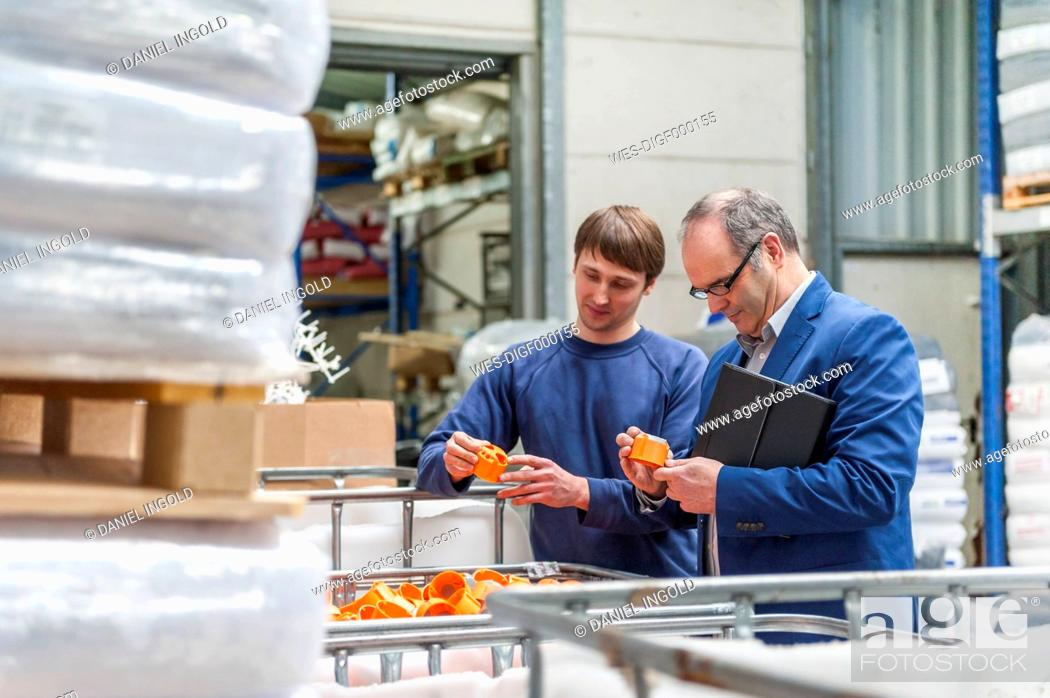 Stock Photo: Manager and worker in storage of plastics factory checking products.