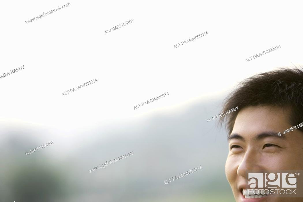 Stock Photo: Young man smiling, cropped view of face.
