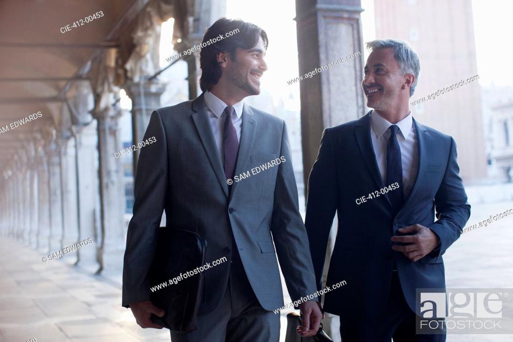 Stock Photo: Smiling businessman walking along corridor.