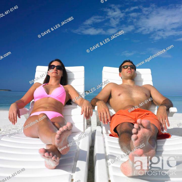 Stock Photo: Couple sunbathing on the beach.
