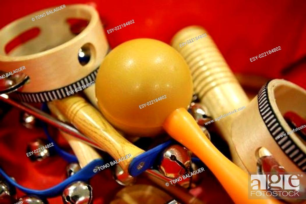 Imagen: mixed percussion toy instruments on red.