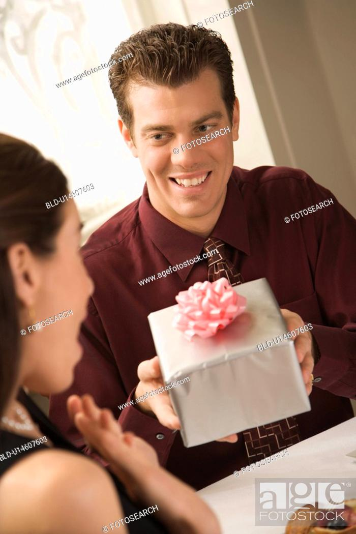 Stock Photo: Mid adult Caucasian man presenting wrapped gift to surprised woman at restaurant.