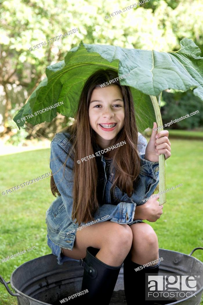 Stock Photo: Portrait of smiling girl under big leaf sitting in tub in the garden.