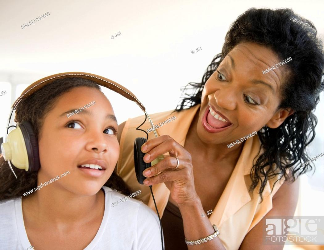 Stock Photo: Mother shouting at daughter listening to headphones.