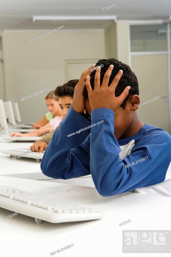Stock Photo: School children 10-13 in computer room, boy under stress head in hands.