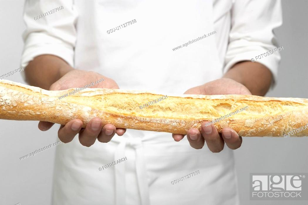 Stock Photo: Chef holding baguette (mid section).