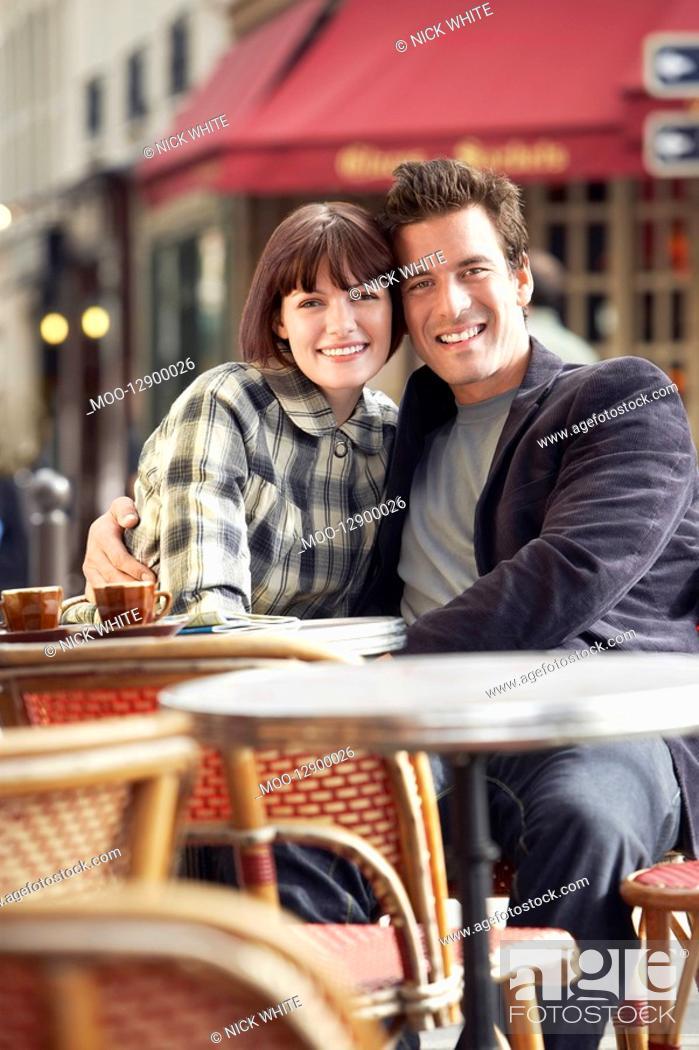 Stock Photo: France Paris Couple sitting outside cafe.