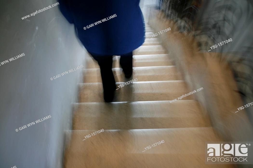 Stock Photo: one person walking down steps in building.