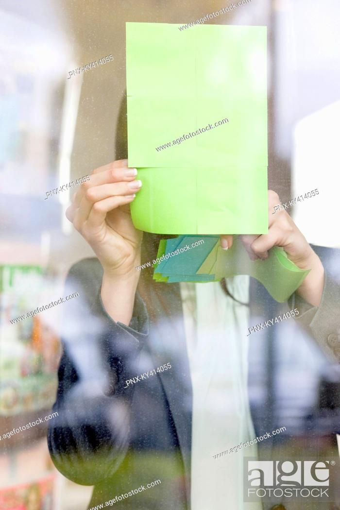 Stock Photo: Businesswoman sticking memo notes on glass in an office.
