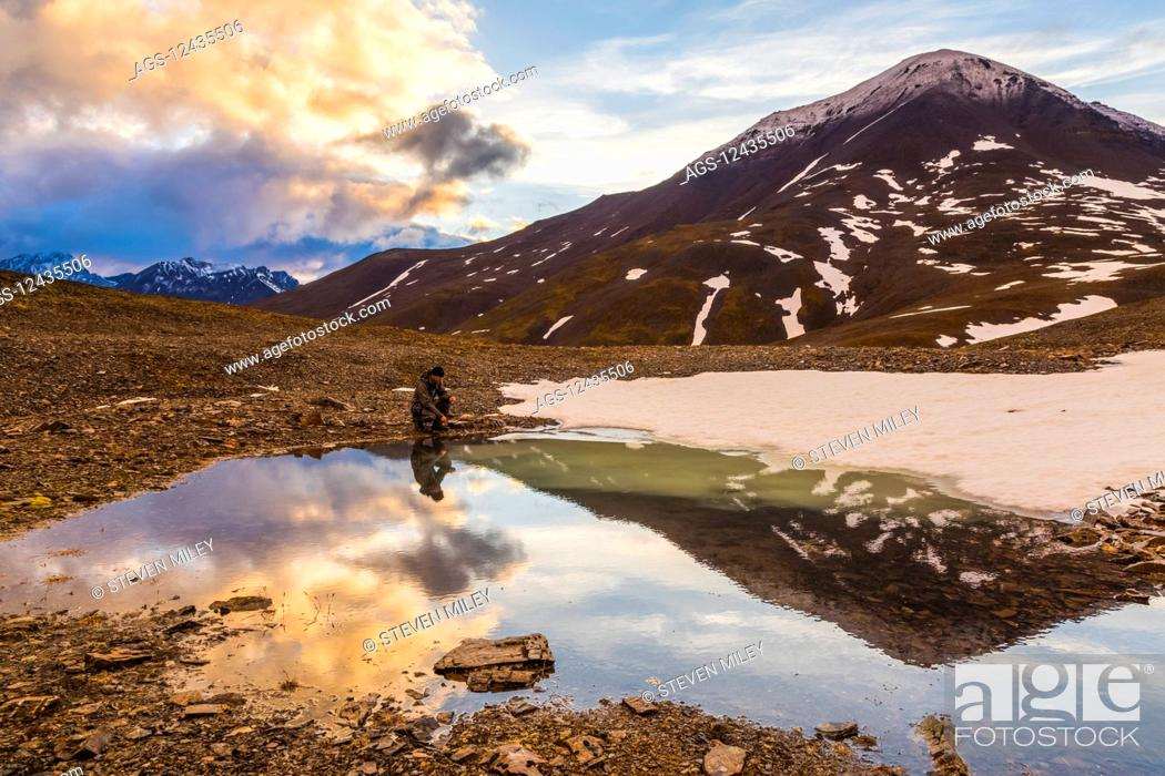 Photo de stock: A backpacker pauses for rest beside a puddle while crossing over an unnamed pass in the Brooks Range under the midnight sun at 12:14 a.m.