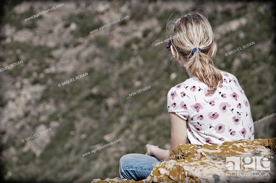 Stock Photo: Blonde girl teen, back looking at the landscape in Gátova, Valencia, Spain.