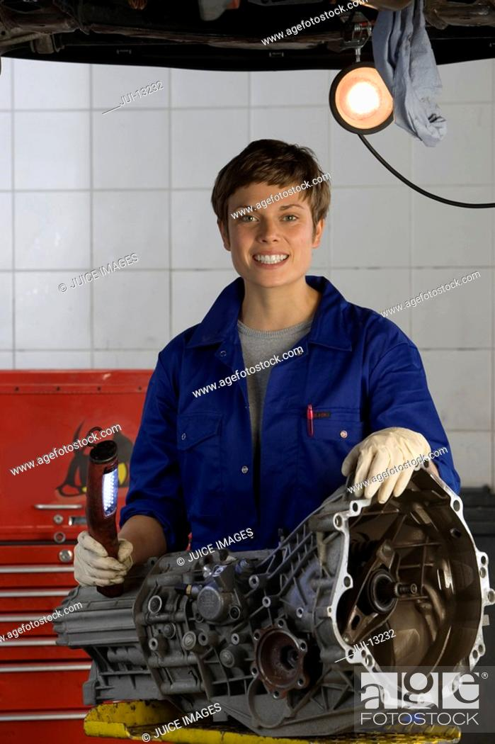 Stock Photo: Female mechanic with engine part by elevated car, smiling, portrait.