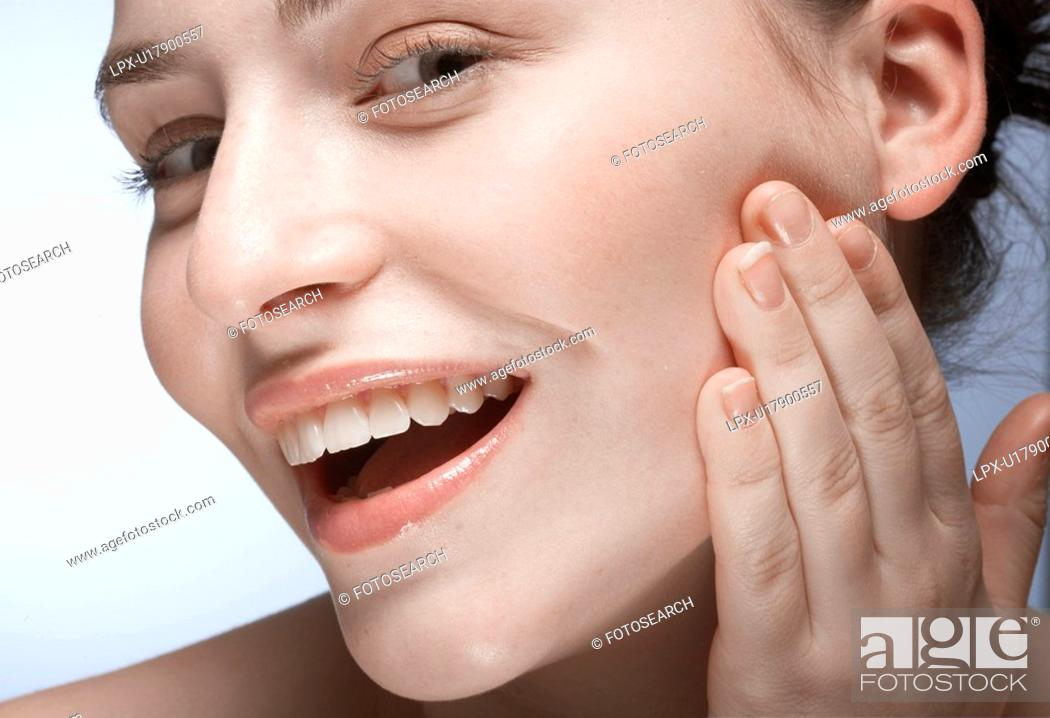 Stock Photo: Woman with hand on face.