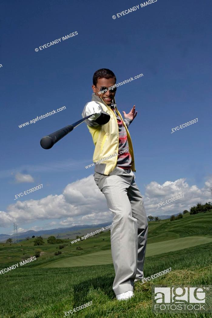 Stock Photo: Portrait of a young man posing with a golf club.