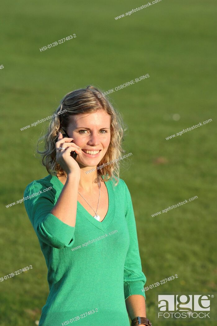 Stock Photo: Young blonde woman outdoors talking on cellphone.