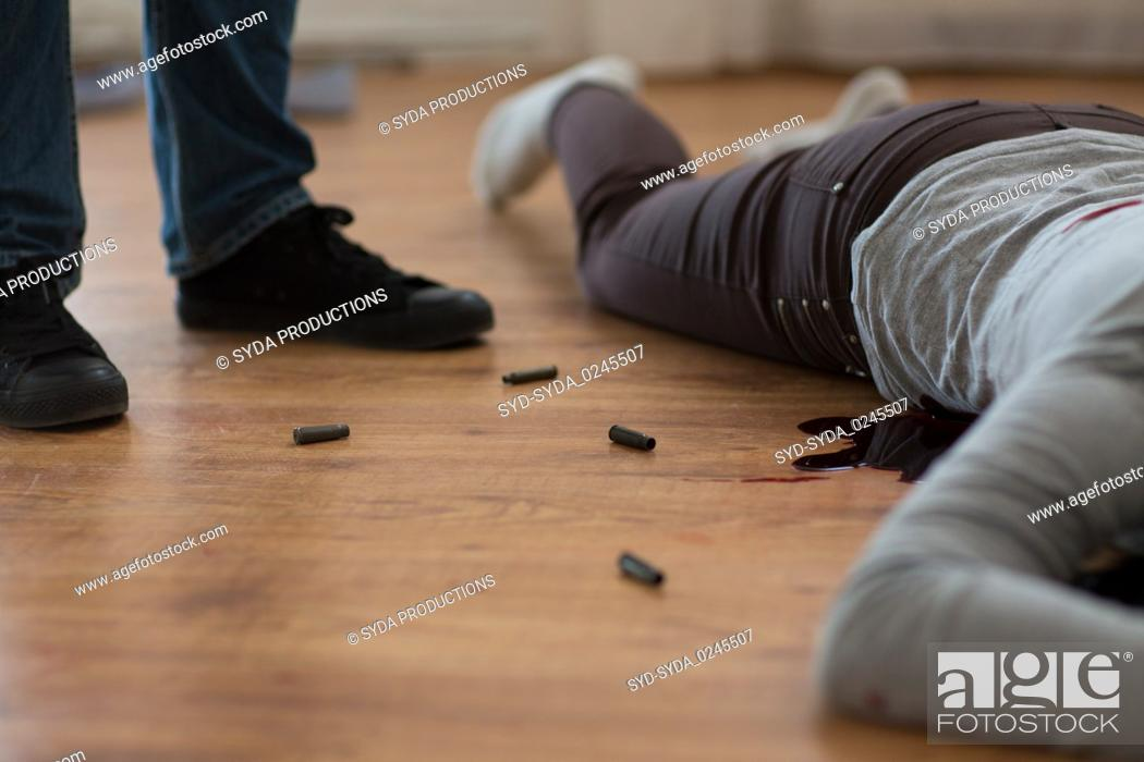 Stock Photo: criminal with dead body and bullets at crime scene.