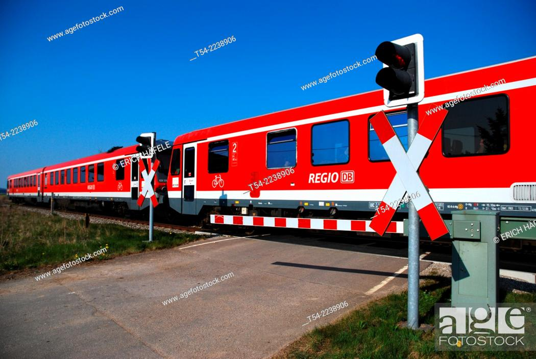 Stock Photo: Train passes through a closed level crossing.