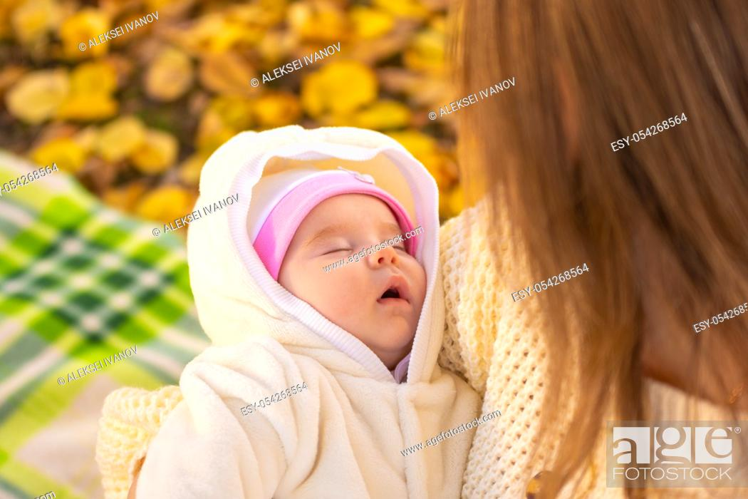 Stock Photo: Two-month-old baby sleeps in mom's arms.