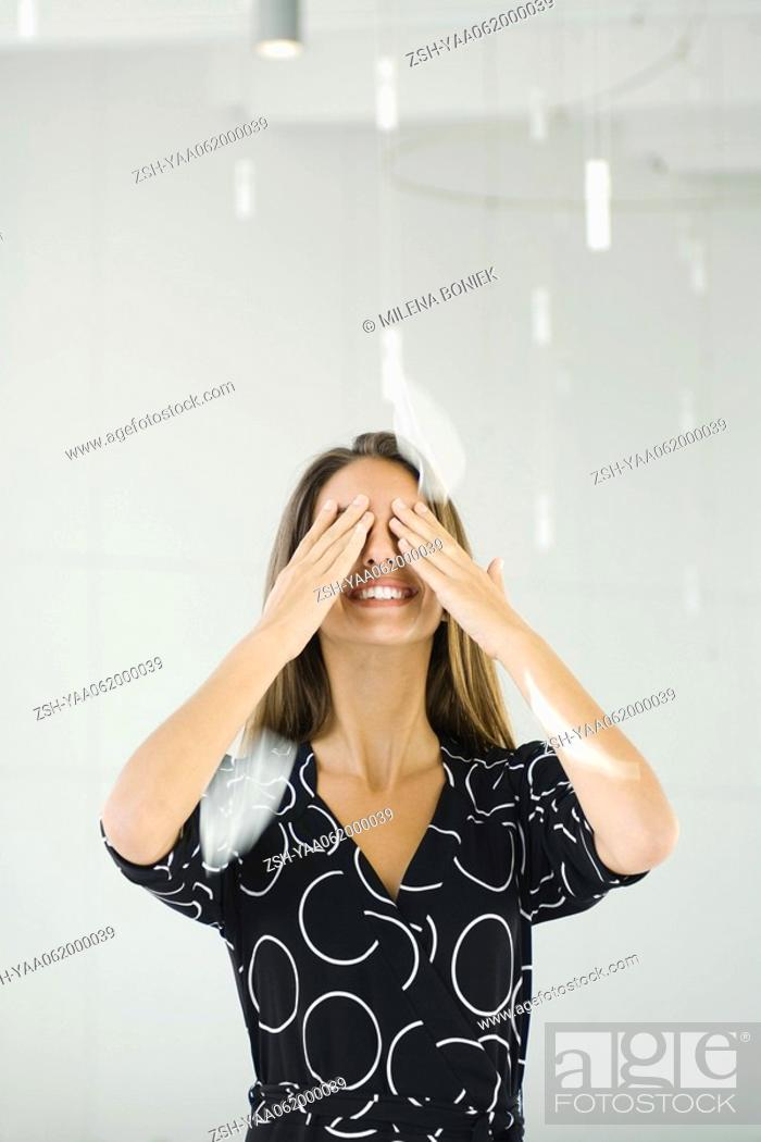Stock Photo: Teenage girl covering eyes with hands, smiling, feathers falling around her.