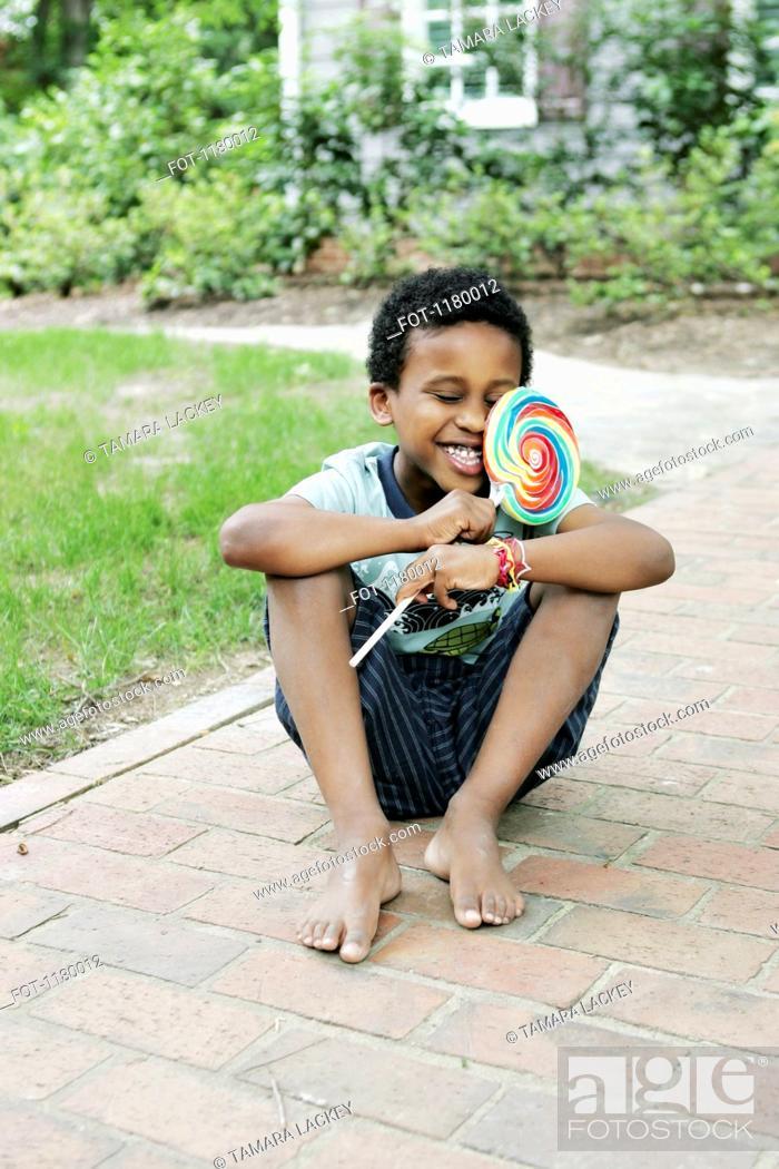 Stock Photo: A smiling boy hugging a swirl lollipop.