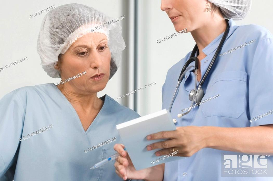 Stock Photo: Two male surgeons discussing a medical report.