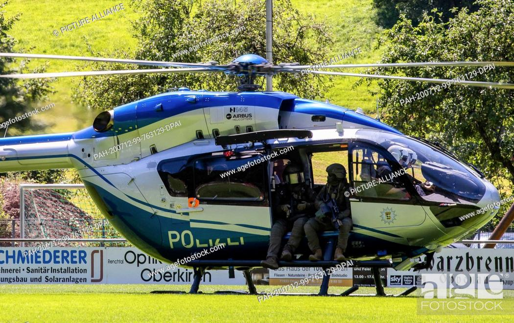 Stock Photo: 12 July 2020, Baden-Wuerttemberg, Oppenau: Police officers of a SEK are sitting in the door of a helicopter that has just landed.