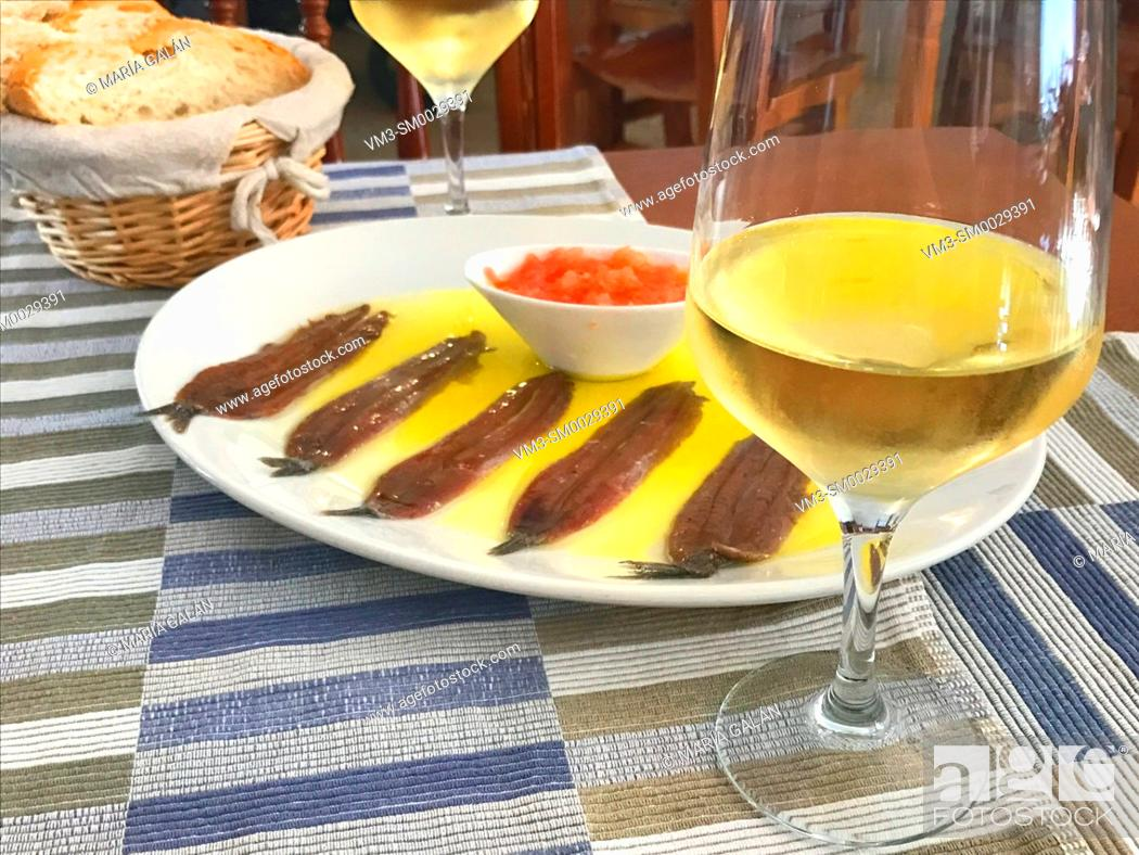 Stock Photo: Glass of white wine and anchovy fillets serving. Spain.