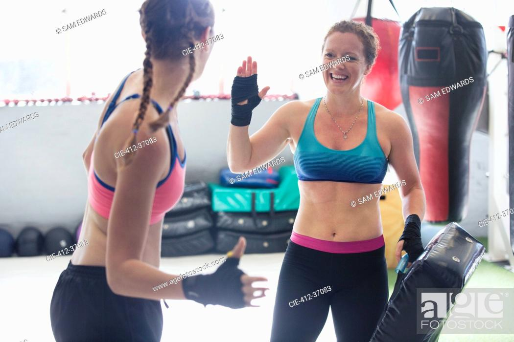 Stock Photo: Smiling female boxers high-fiving in gym.