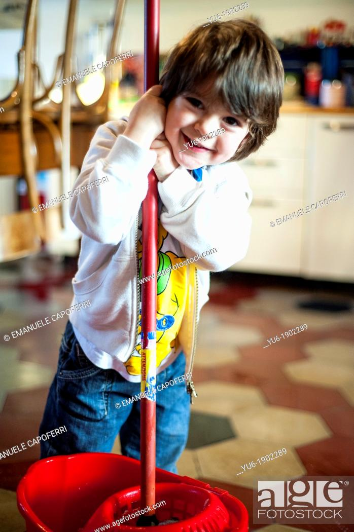 Stock Photo: child with bucket and mop in the kitchen.