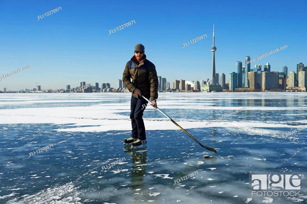 Imagen: Hockey player and city skyline from Ward's Island; Toronto, Ontario, Canada.