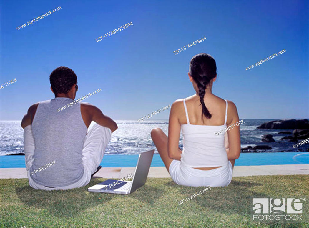Stock Photo: Rear view of a young couple sitting on a lawn with a laptop.
