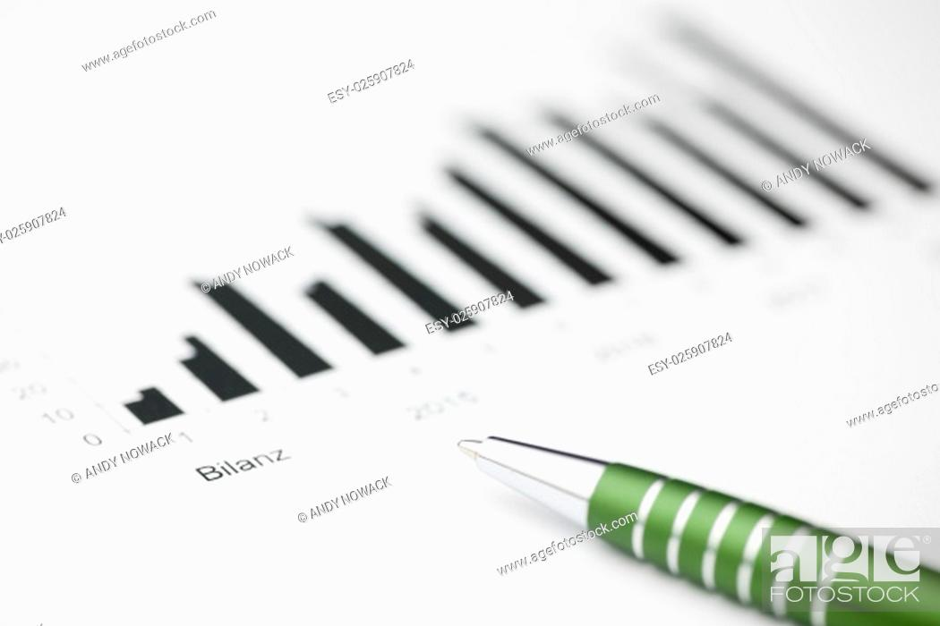 Stock Photo: closeup of lying on a balance chart green pen in the short focus.
