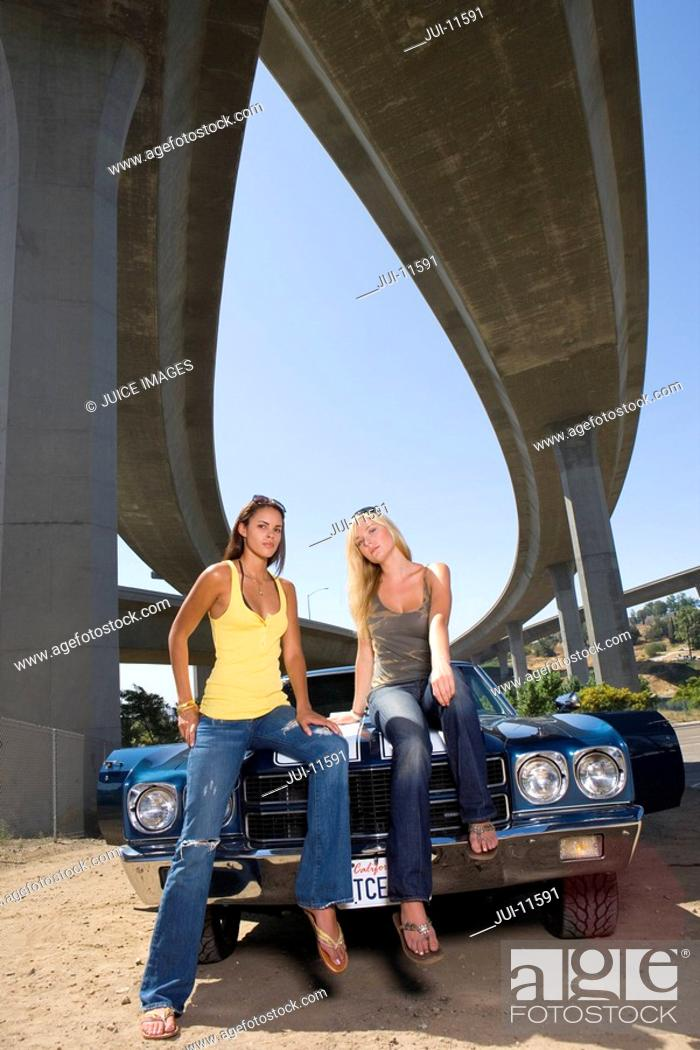 Stock Photo: Two young women on bonnet of car beneath underpass, low angle view.