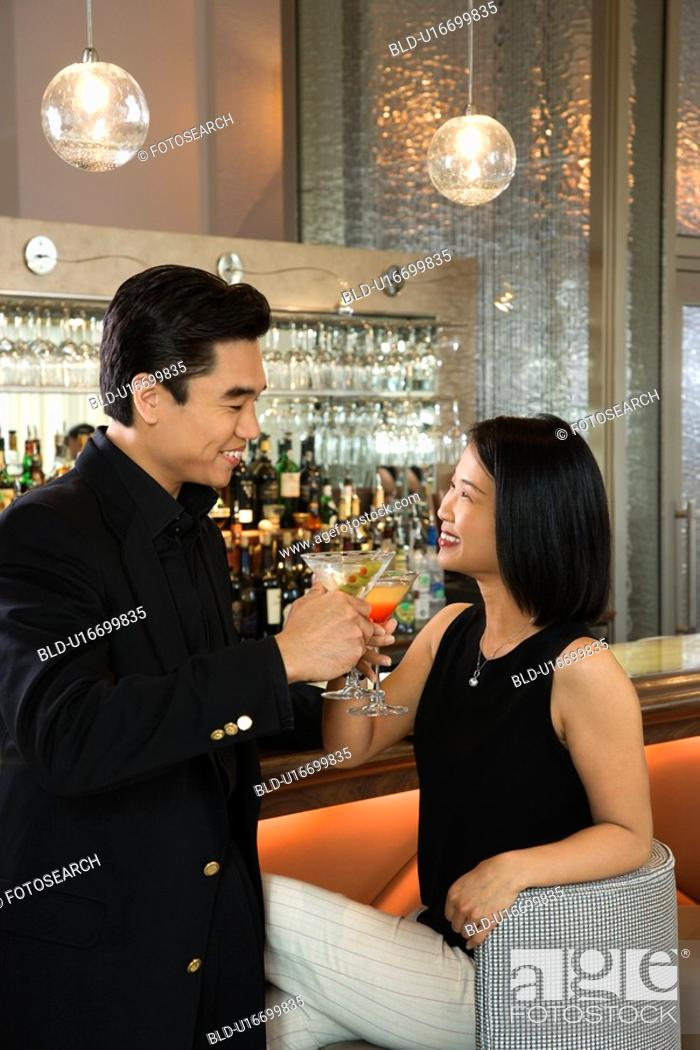 Stock Photo: Prime adult Asian male and female at bar with cocktails.