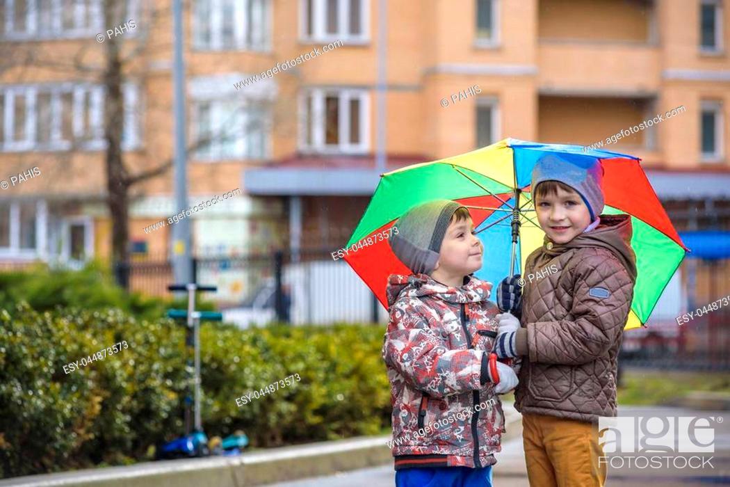 Imagen: Two little boys, squat on a puddle, with little umbrellas. frienship communication concept.