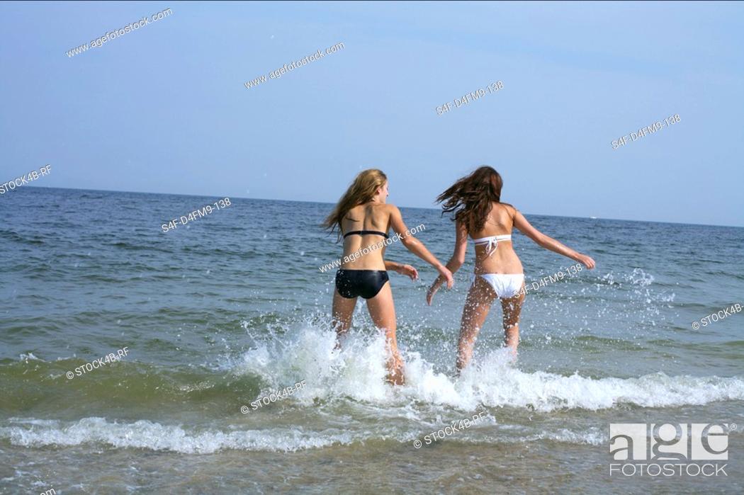 Stock Photo: Two young women in bikini running into the sea, blurred motion.