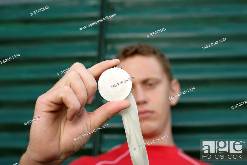 Stock Photo: Young man in front of a wall made of corrugated sheet iron holding aup a medal, selective focus.