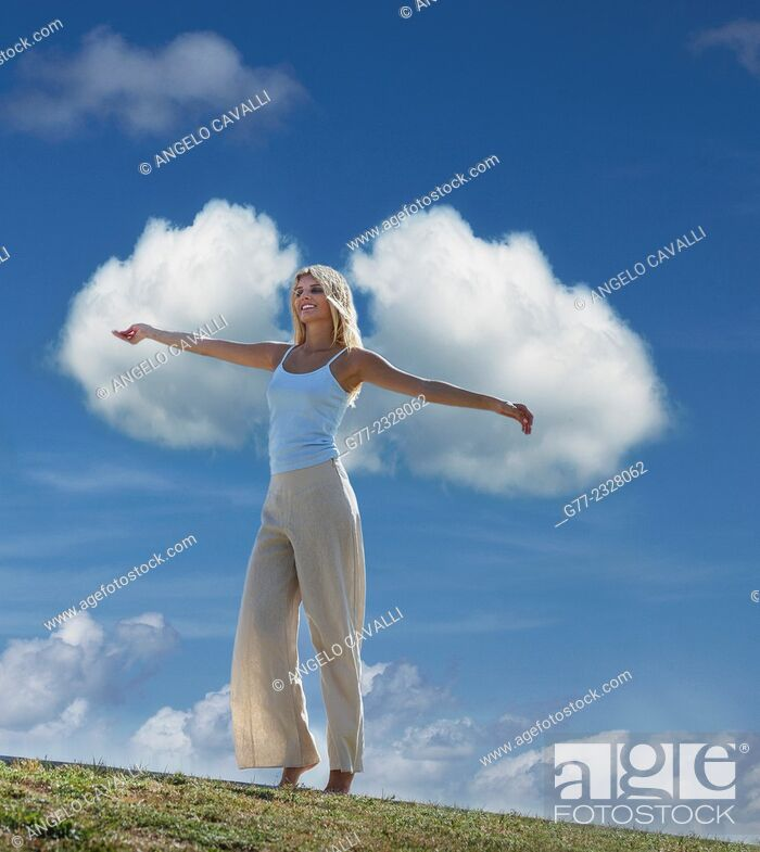 Stock Photo: Young woman with open arms against clouds in the sky, Miami Beach, Florida, USA.