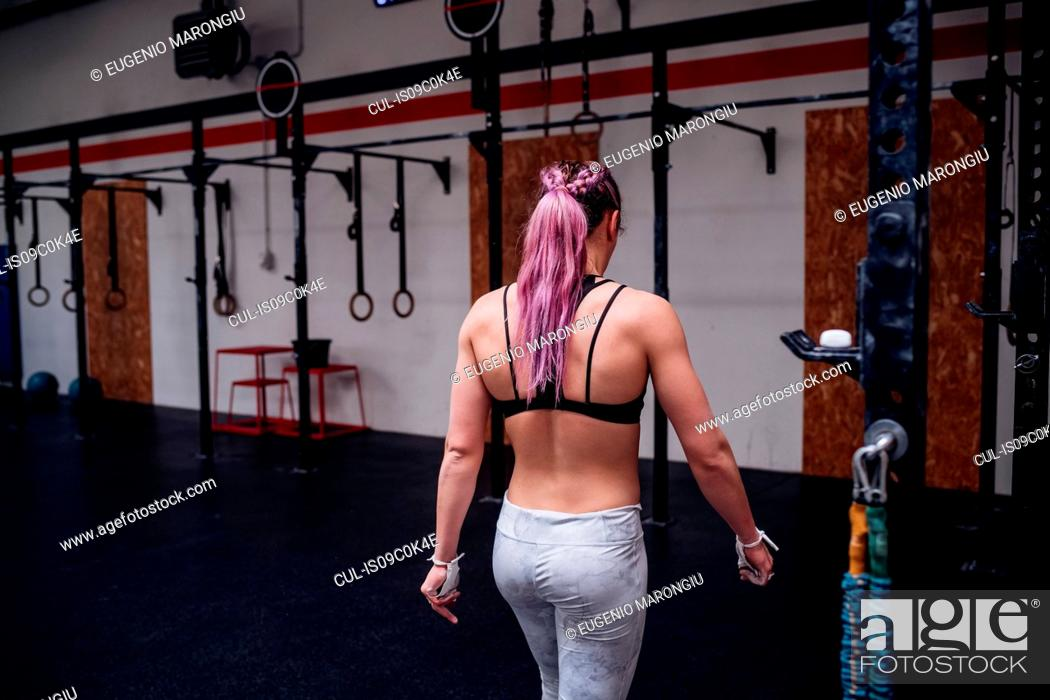 Imagen: Young woman with purple ponytail training in gym, rear view.