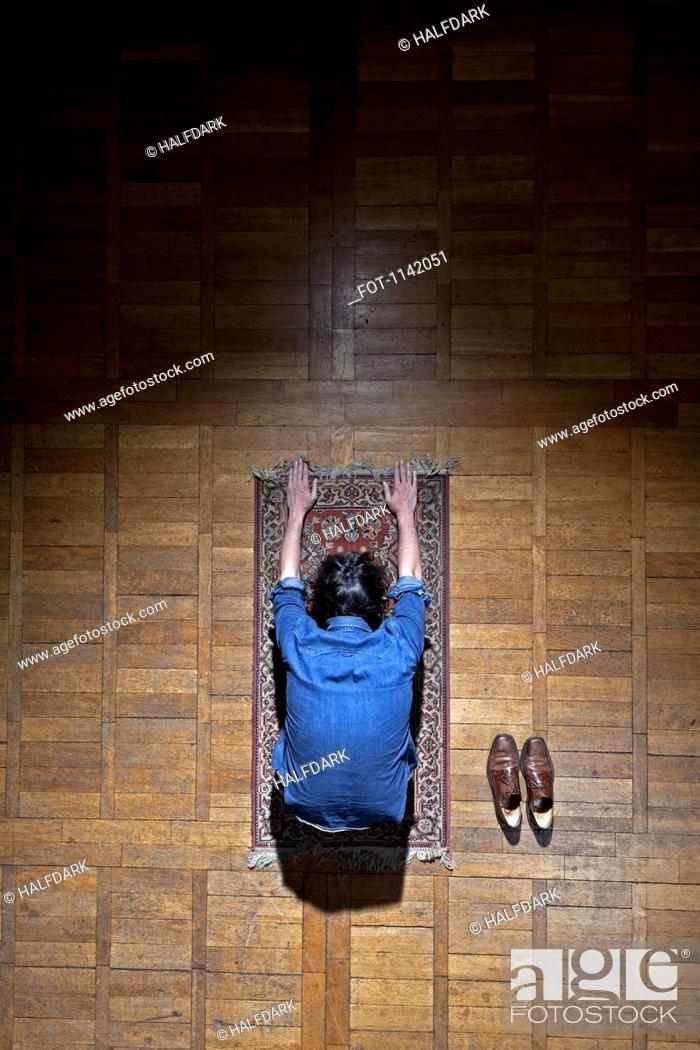 Stock Photo: A man praying on a mat.