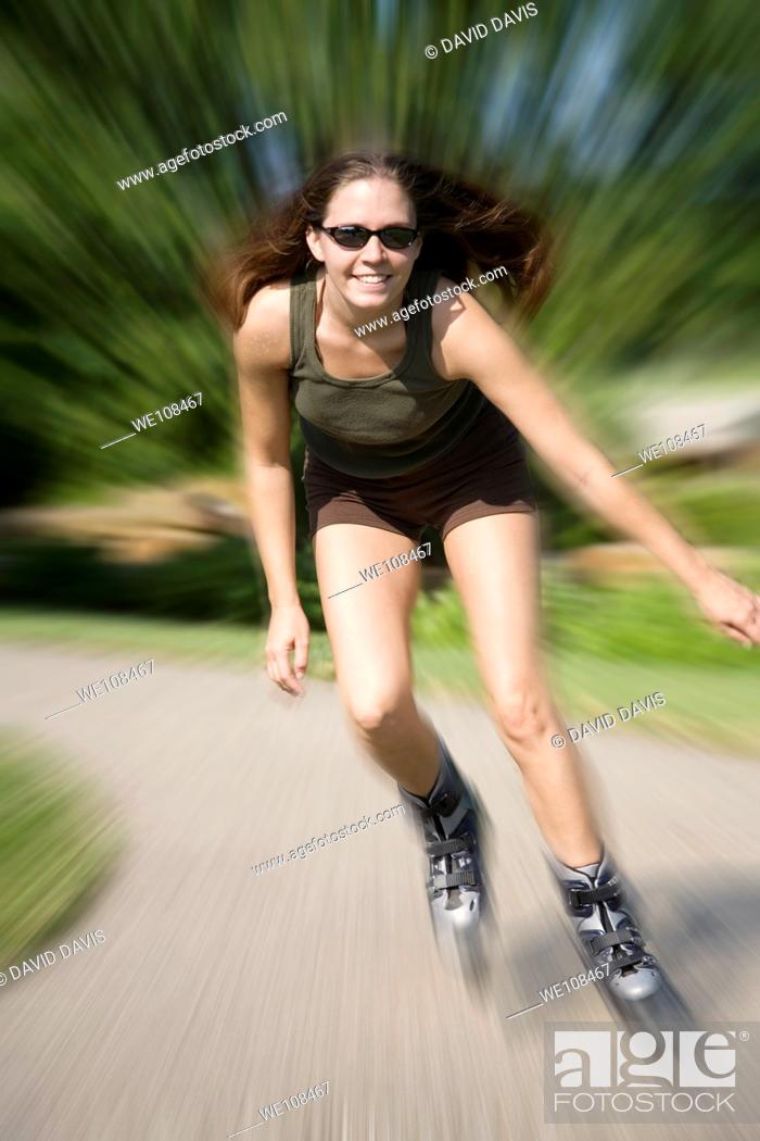 Stock Photo: Young woman in early 20s roller blading in park.