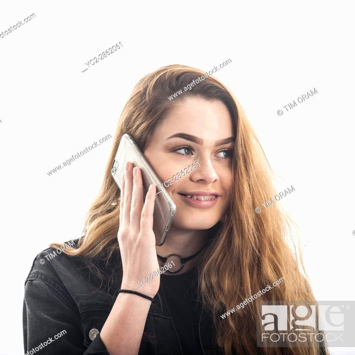 Stock Photo: A pretty 15 year old girl speaking on smartphone looking happy in the studio against a white backdrop in the Uk.