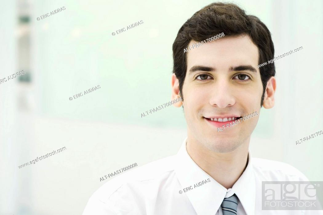 Stock Photo: Young businessman smiling at camera, portrait.