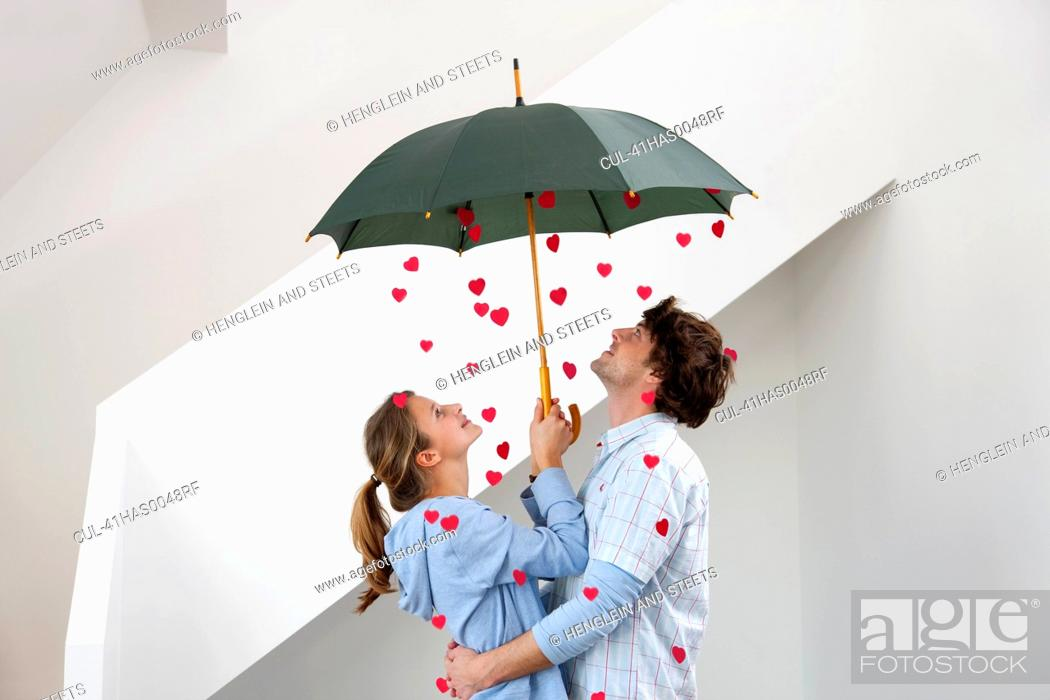 Stock Photo: Couple standing under shower of hearts.