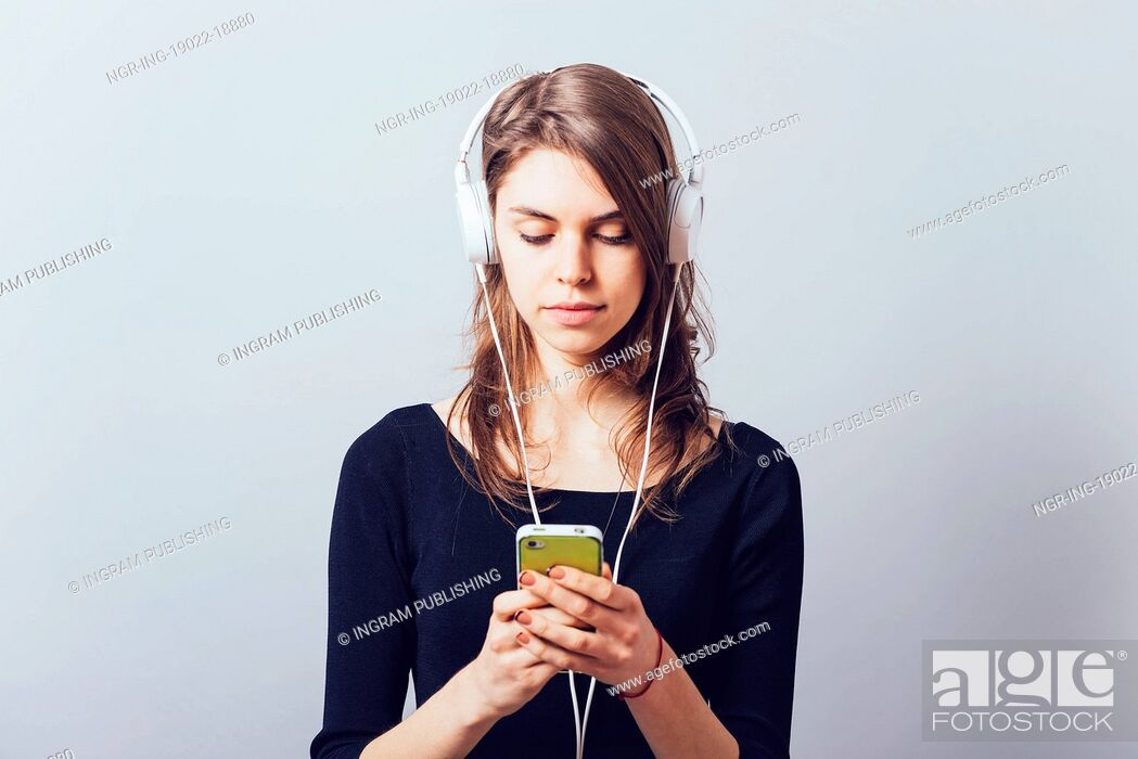 Stock Photo: Woman with headphones and listening to music on a grey background.